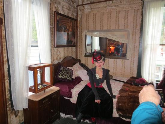 During a tour, one of the employees sat on the bed of one of the rooms of the former madams