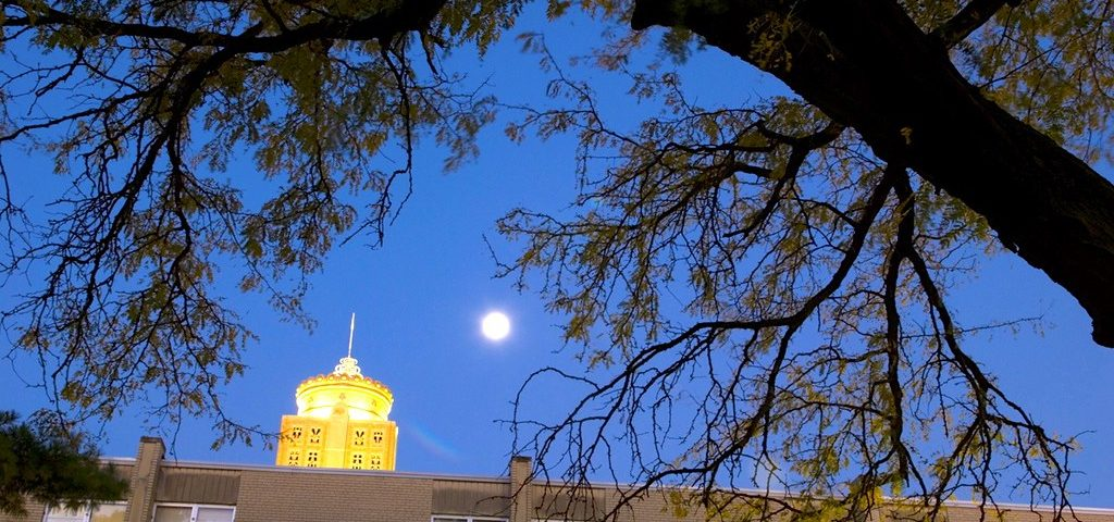 A photo of the St. Ambrose University and a full moon
