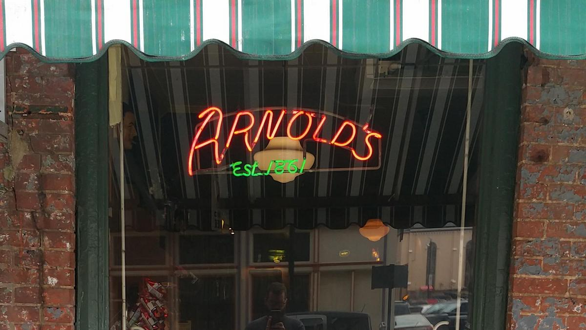 A sign on the window of Arnold's Bar and Grill