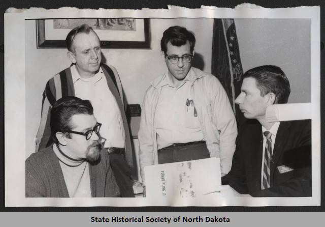 Frank Vyzralek and James Sperry in an undated photo with some of their co-workers