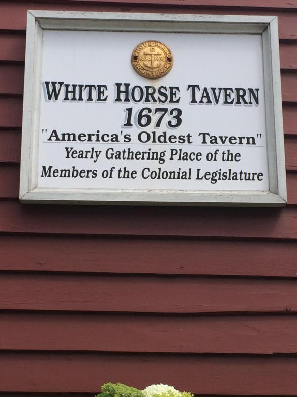 A sign showing the White Horse Tavern recognized as the oldest tavern in the United States